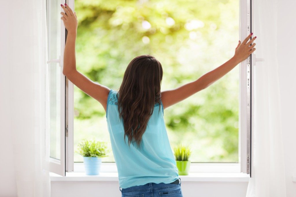 woman letting air and light in by opening window