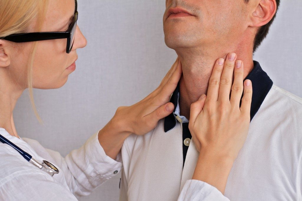 Doctor touching a man's neck