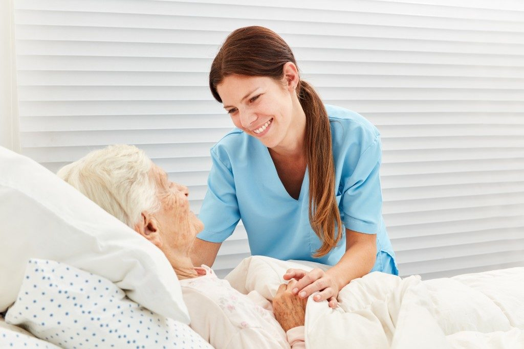 nurse attends to a woman in palliative care