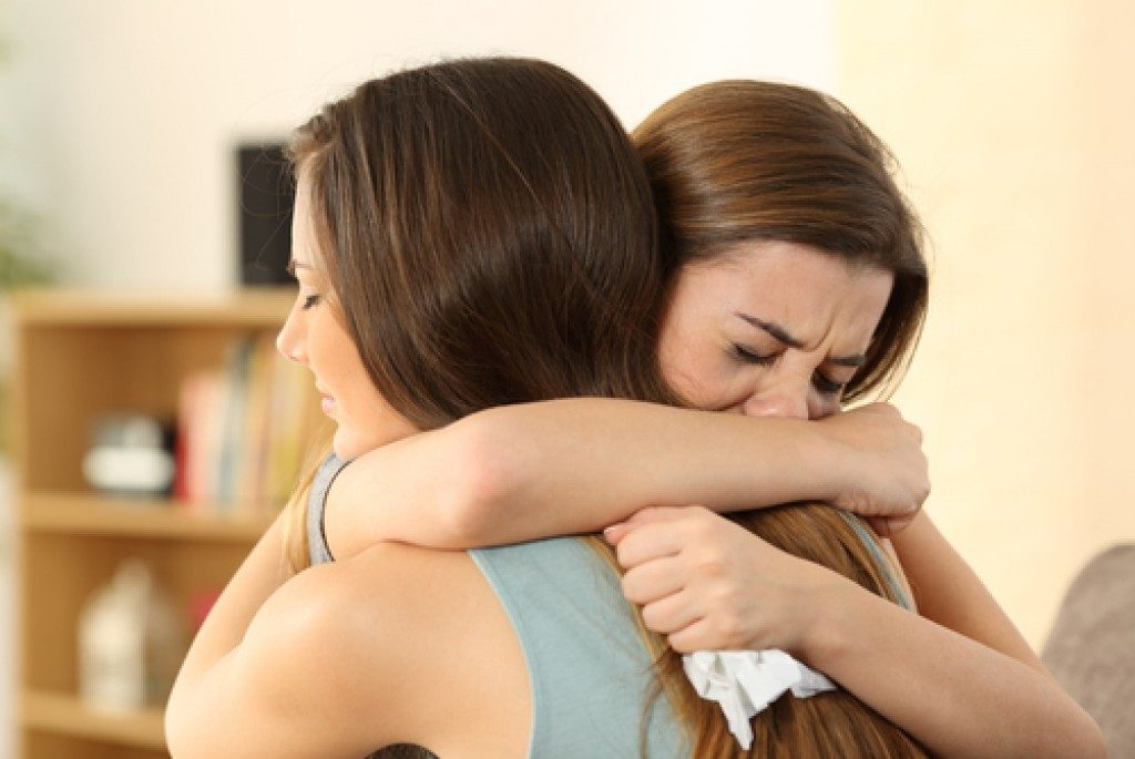 Woman hugging her grieving friend