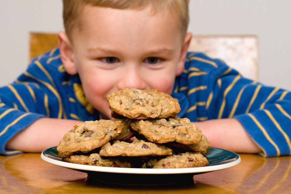 little boy staring at plate of cookies