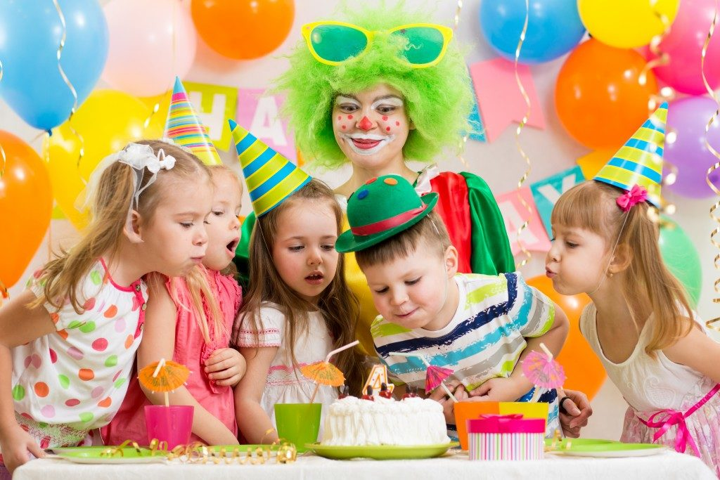 kids blowing a birthday cake