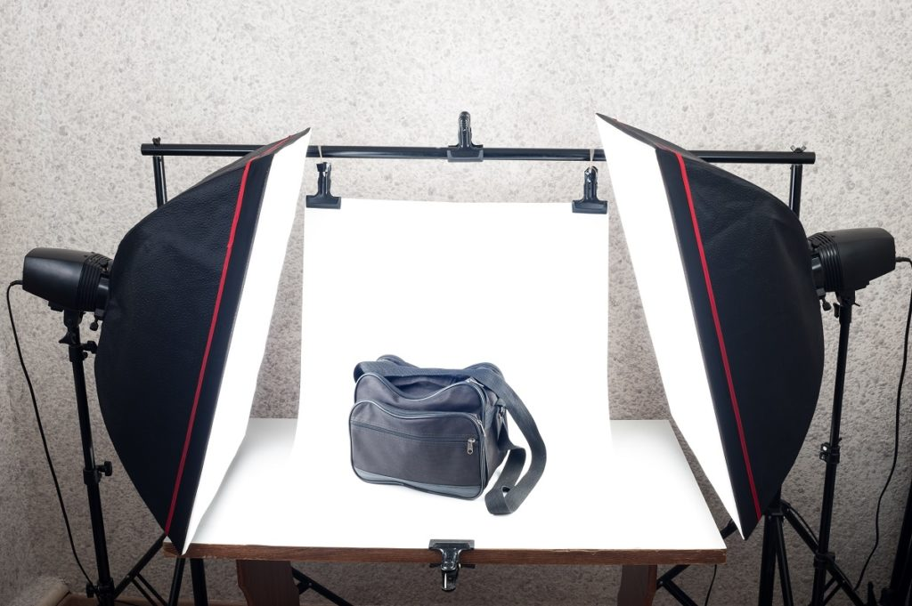 a black messenger bag being photographed in a studio