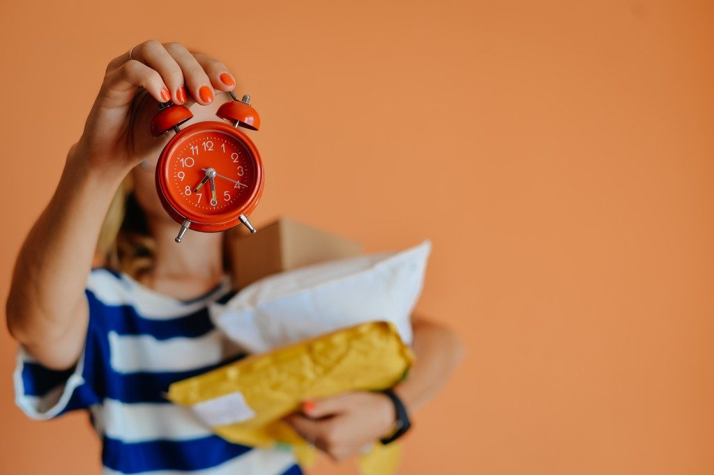 holding an alarm clock