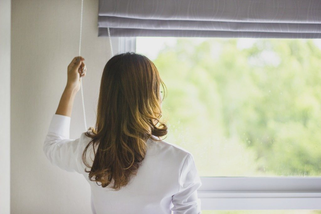 woman drawing the blinds
