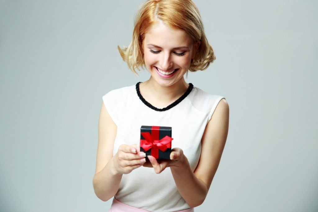 Smiling beautiful young woman holding an open jewelry gift box