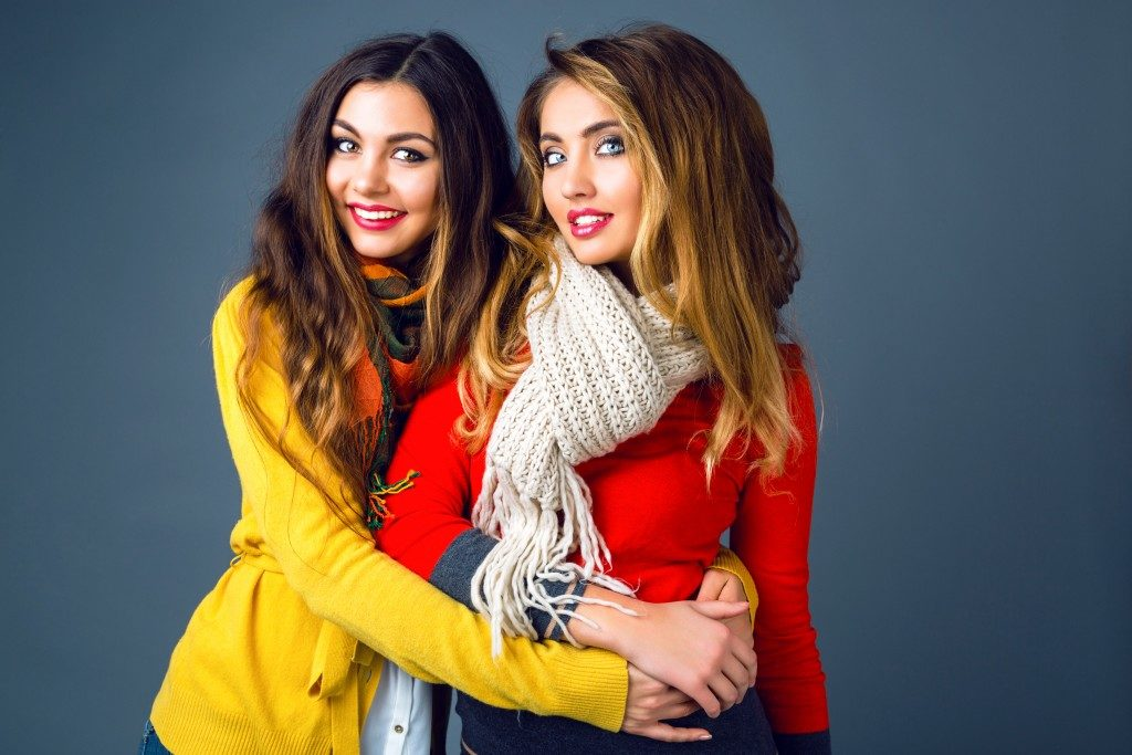 best friends wearing bright stylish cashmere sweaters and scar