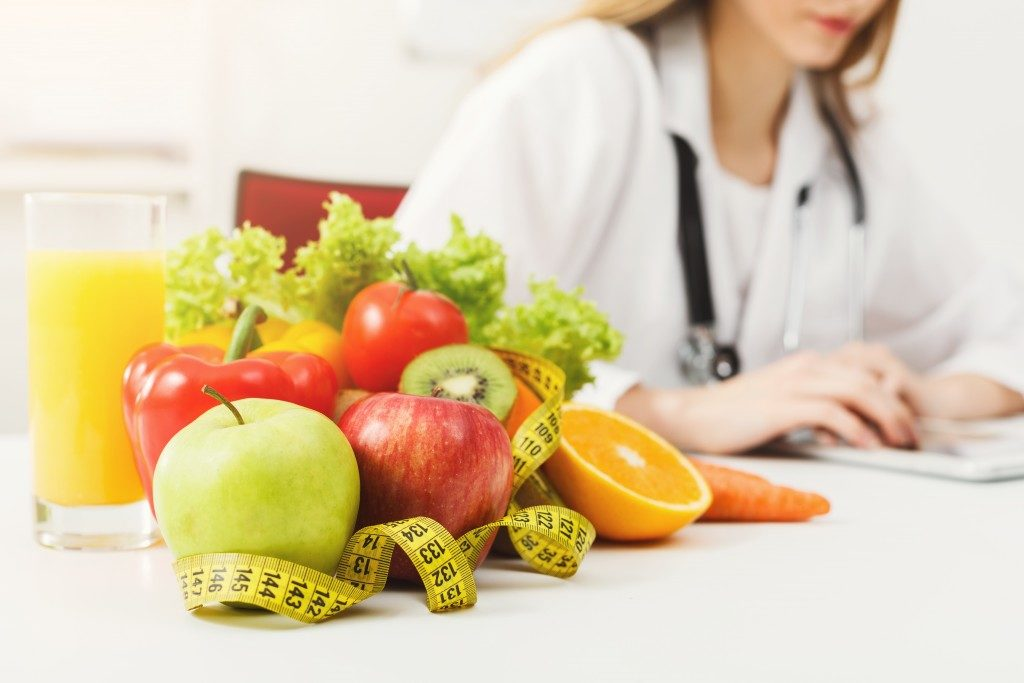 fruits next to measuring tape and doctor