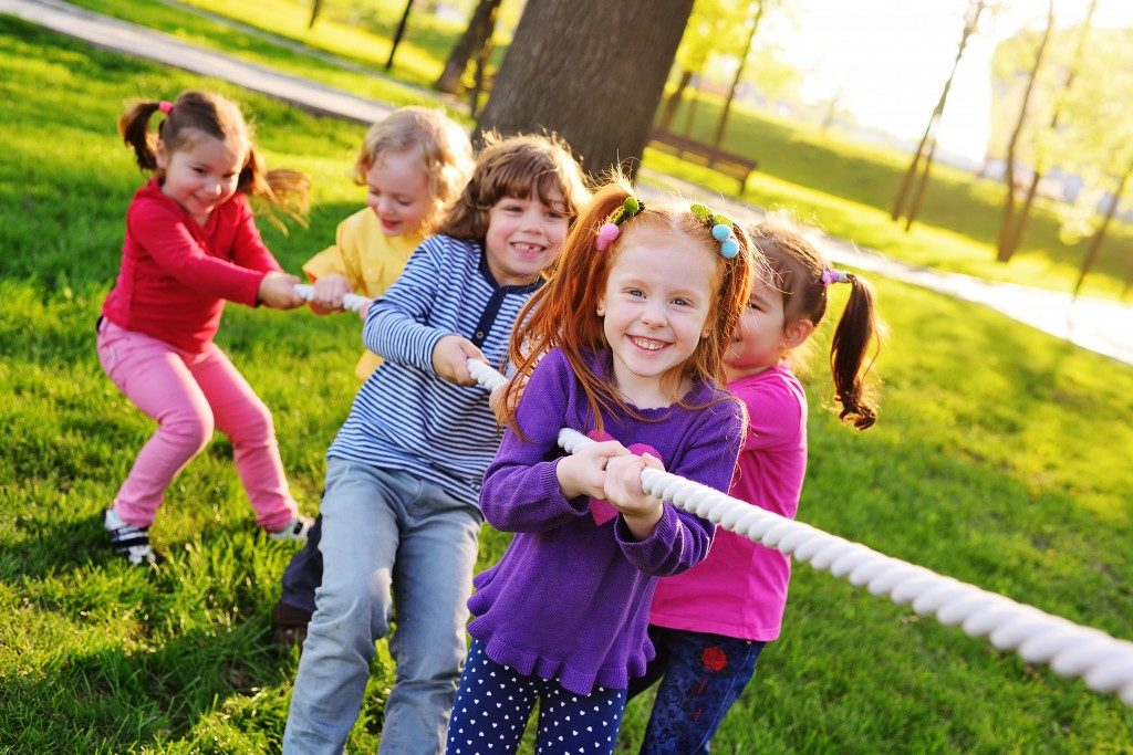 kids pulling a rope in the park