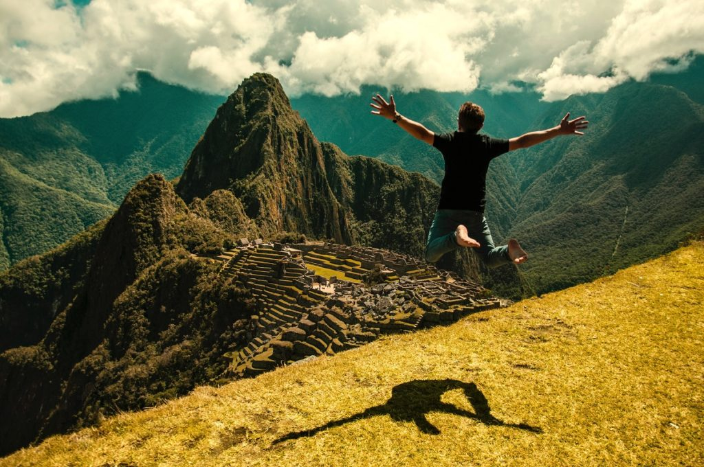 man doing a jump shot near machu picchu