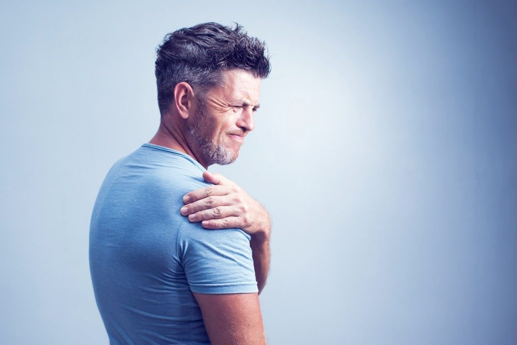 man experiencing muscle pain in the shoulder area
