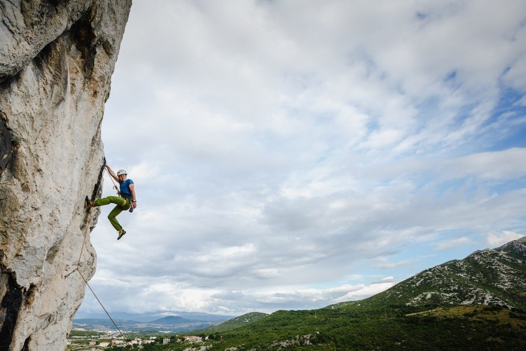 male climber hanging by a cliff