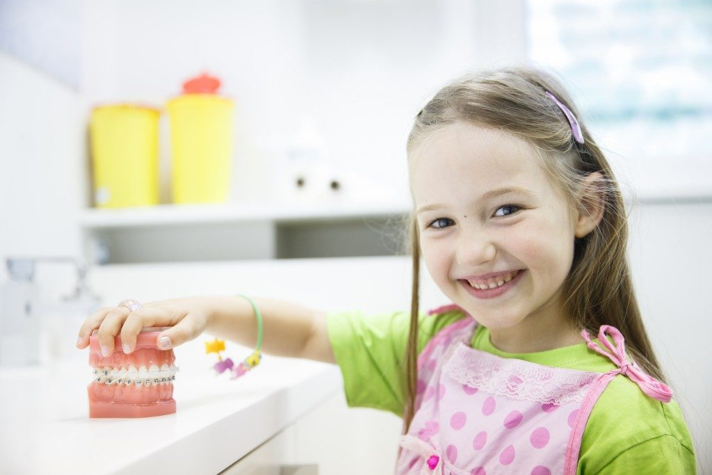 child at the dental office with teeth model