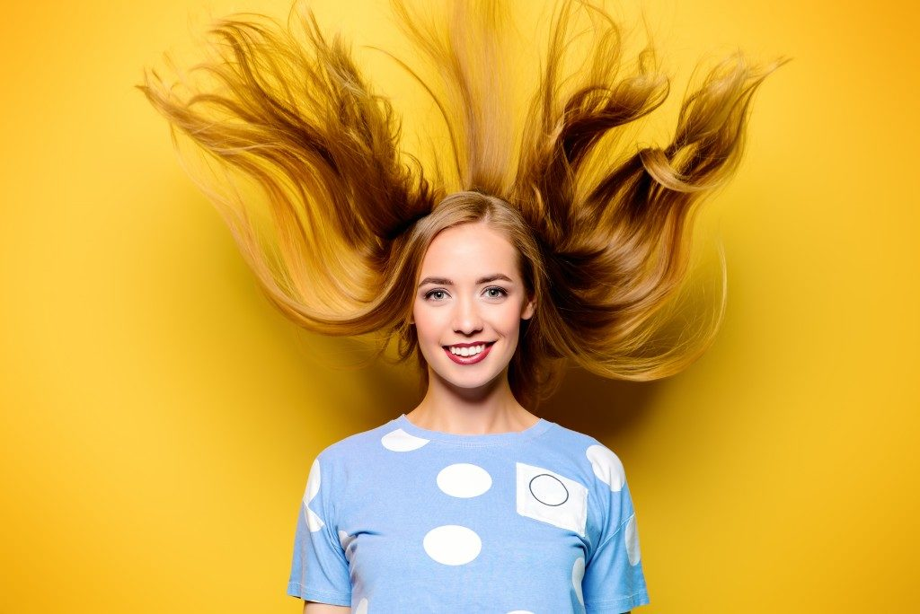 woman with blond hair over a yellow background