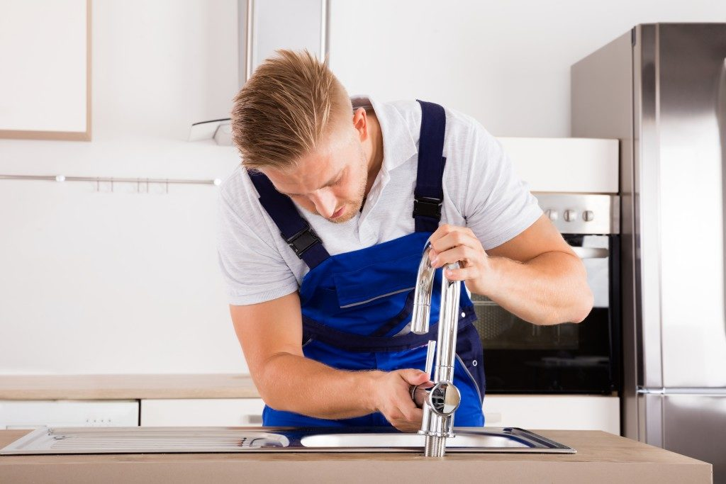 plumber fixing the faucet