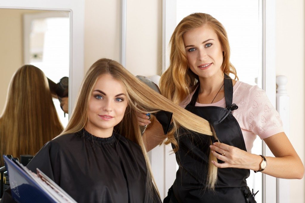 hairdresser holding scissors, comb and hairdryer in hands and picking proper hairdo to smiling long haired customer