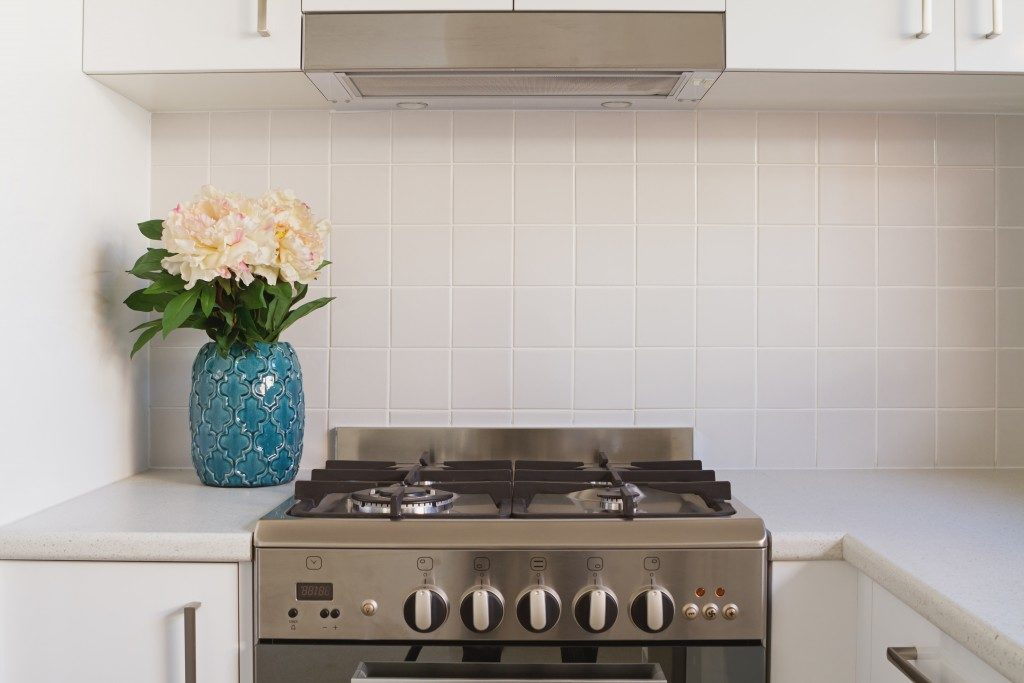 Close up of kitchen oven and tiled splashback with a pot of flowers