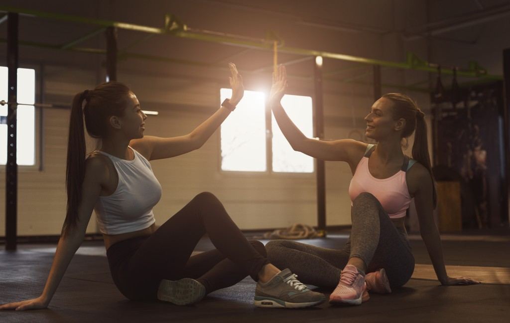Two women doing a high-five after working out