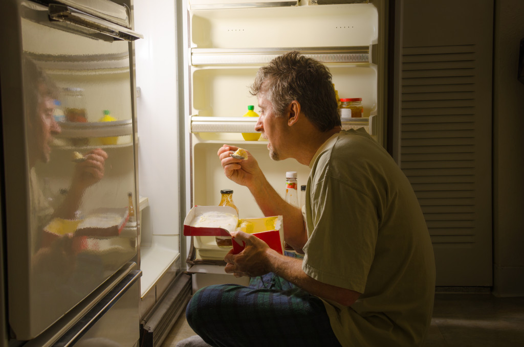 eating as he sits in front of a refrigerator