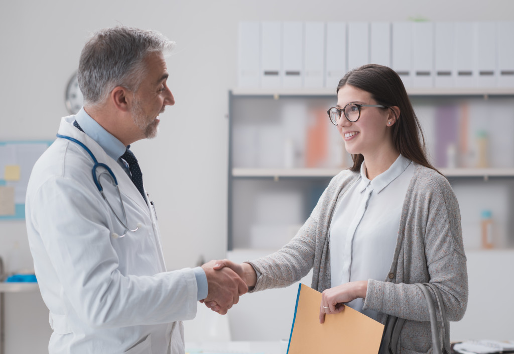 woman shaking doctor's hand