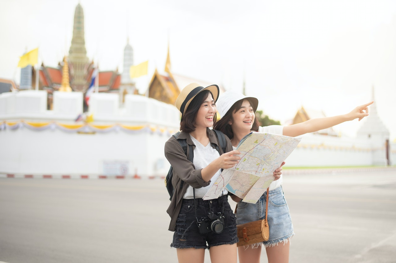 2 women holding map travelling