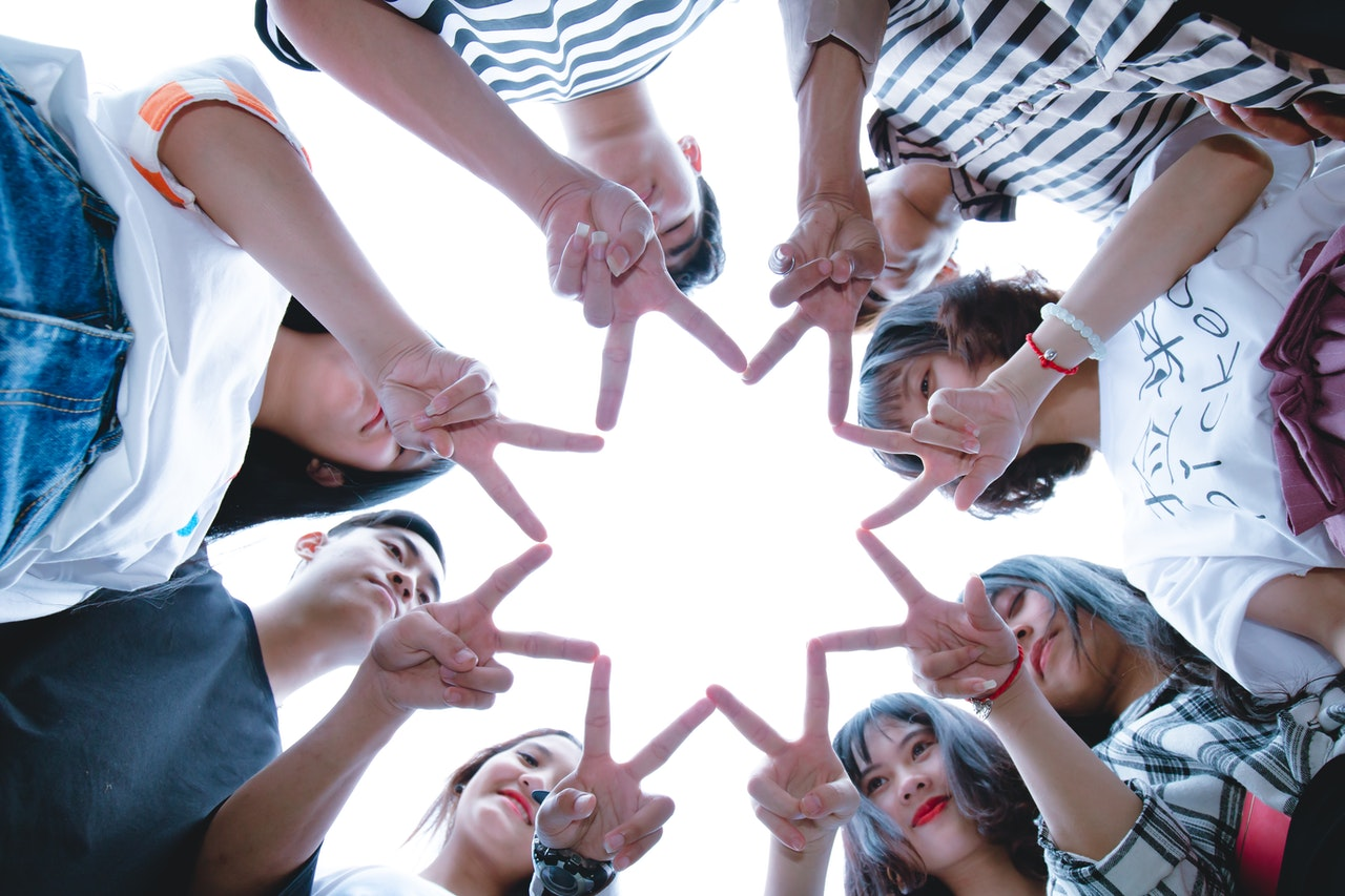 young adults making a star with their fingers
