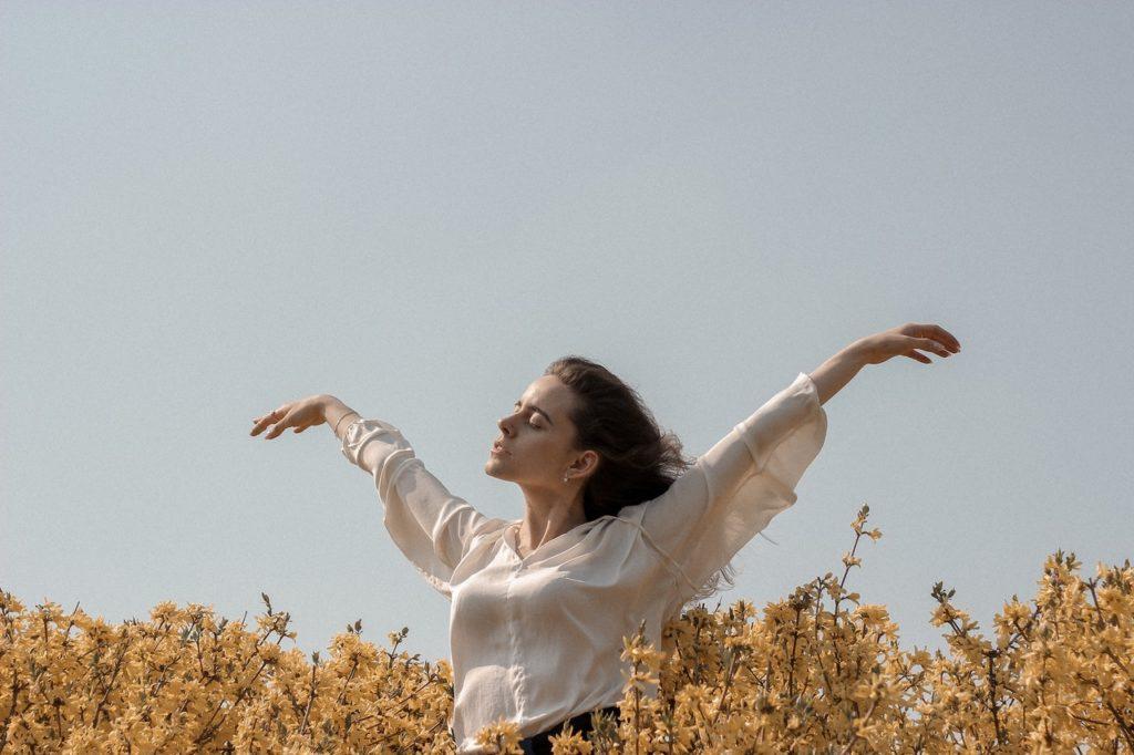 woman feeling the wind on a field