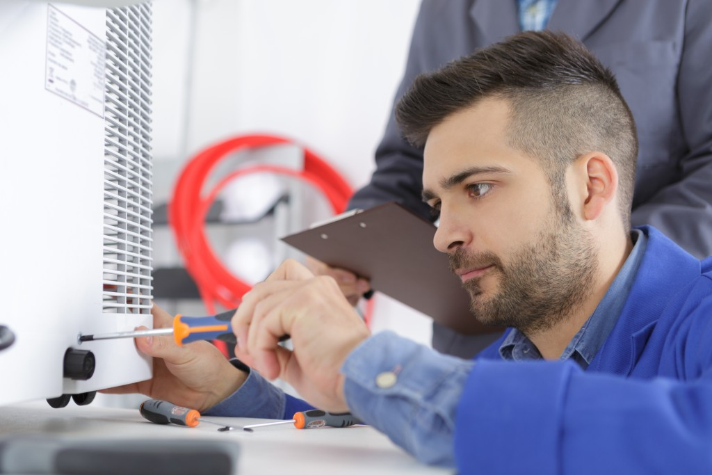 man fixing an air conditioning unit