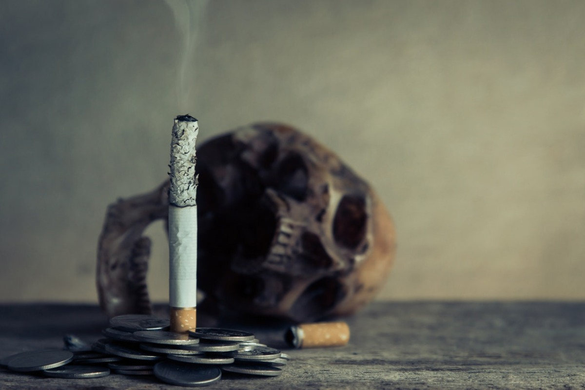 a cigarette, coins, and a skull