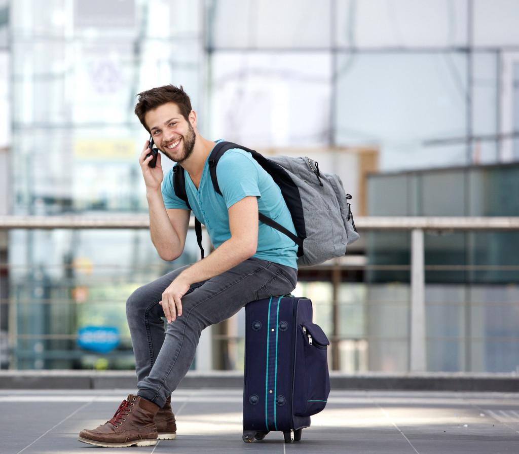 man sitting on his luggage