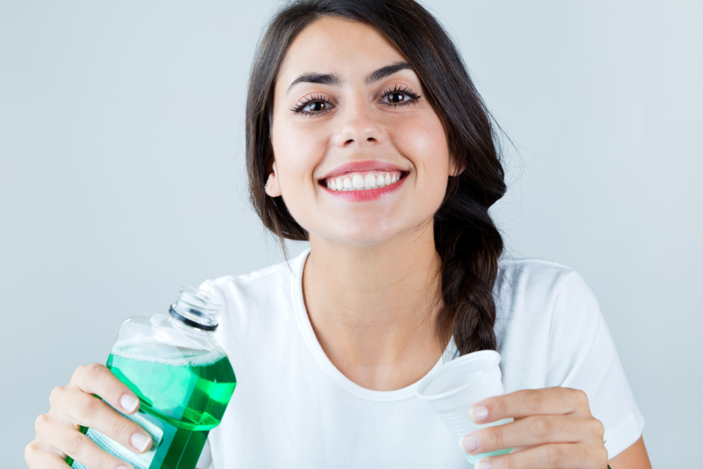 woman holding a bottle of mouthwash